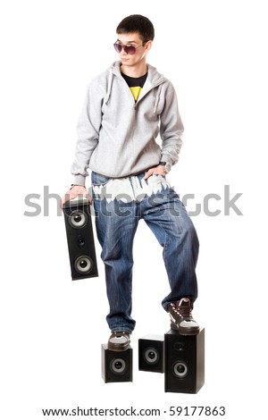 Young man in sunglasses standing on the speakers - stock photo