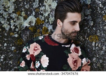 Young man in sweater against rock - stock photo