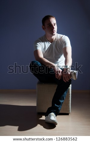 Young man in T-shirt and jeans on dark background