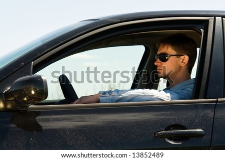 young man in the car at the wheel - stock photo