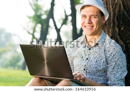 young man in the park sitting on the grass, enthusiastically working with a laptop
