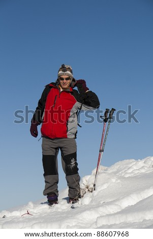 Young man in the snow getting ready for ski - stock photo