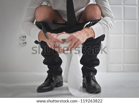 Young man in tie on a toilet holding a roll of toilet paper - stock photo