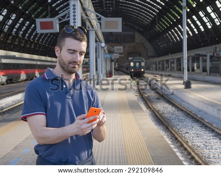 young man in train station using cellphone  - stock photo