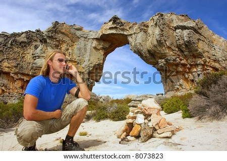 Young man in trendy spectacles talks over phone sitting in front of Wolfberg  Arch. Shot in Cederberg, Western Cape, South Africa.