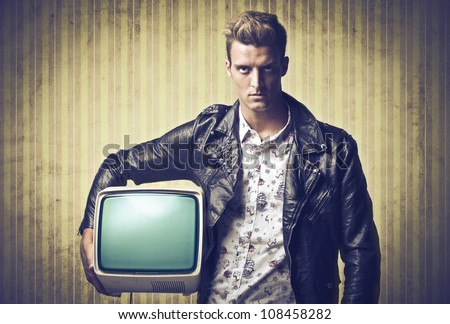 Young man in vintage clothes holding an old television under his arm - stock photo