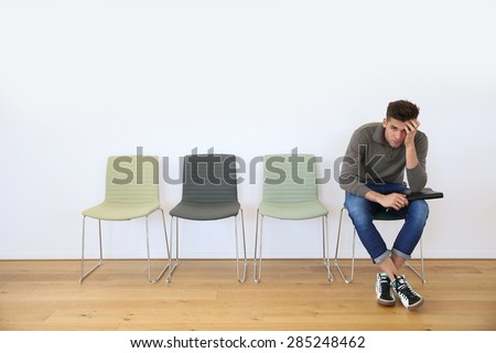 Young man in waiting room for job interview - stock photo