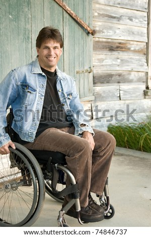 young man in wheelchair, smiling - stock photo