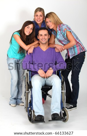 Young man in wheelchair with group of girl friends - stock photo