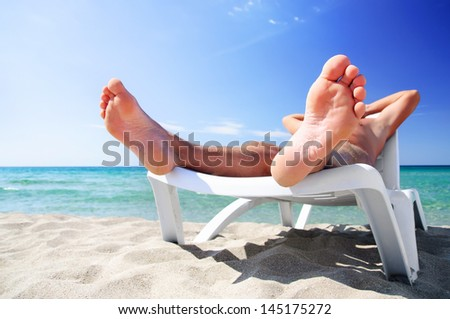 Young man in white cap sunbathe on beach bed at summer sea beach