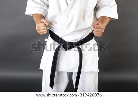 Young man in white kimono and black belt training martial art over gray background - stock photo