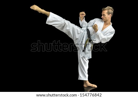 Young man in white kimono training karate. Isolated over black background.