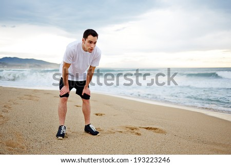 Young  man in white shirt leaning on his knees and breathing hard after a grueling jogging on the beach during a storm - stock photo