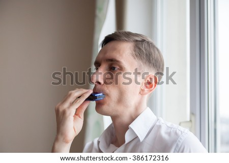 young man in   white shirt playing harmonica.