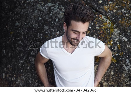 Young man in white t-shirt against rock - stock photo