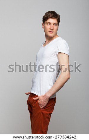 young man in white tshirt and red pants standing on gray background - stock photo