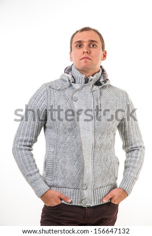 Young man in winter clothes getting cold.  picture of a male fashion model wearing wool sweater.  studio picture of a young man dressed for winter.