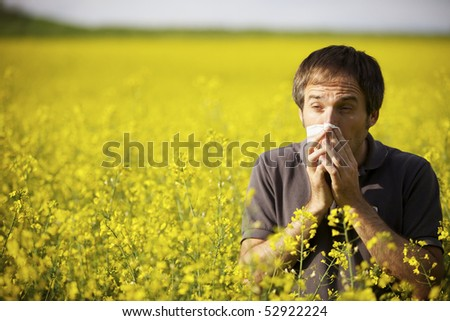 Young man in yellow canola field blowing his nose and suffering from pollen allergy. - stock photo