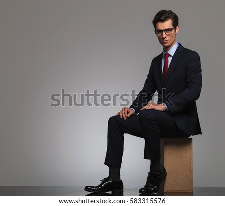 young man ins suit and tie wearing glasses is sitting in studio against grey background
