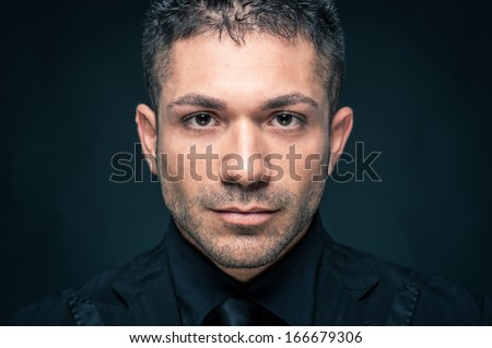 Young man intense close up portrait against dark background.  - stock photo