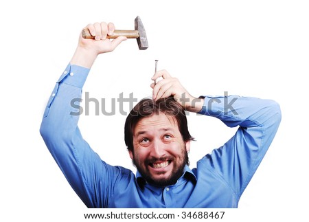 Young man is about to put nail into his head with a hammer - stock photo