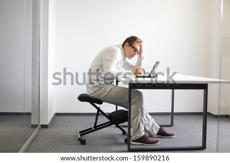 Young man is bent over his tablet in his office,seating on kneeling chair  Bad sitting posture at work - stock photo