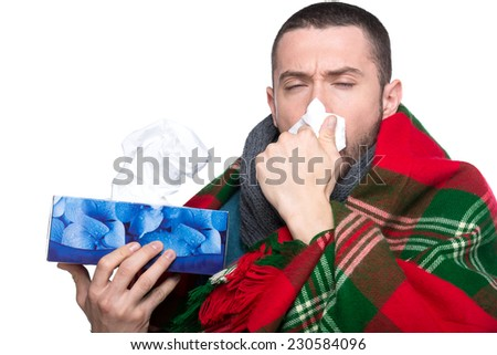 Young man is blowing his nose in a handkerchief isolated on white background. - stock photo