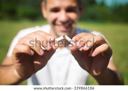 Young man is breaking a cigarette on green background, quit smoking concept - stock photo