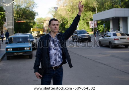 Young man is catching taxi on the street