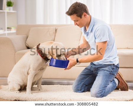 Young man is feeding his dog sitting on the floor in the room. - stock photo
