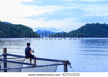 Young man is fishing on wooden coop at the morning - stock photo