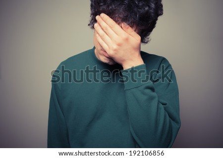 Young man is hiding his face in the palms of his hands - stock photo