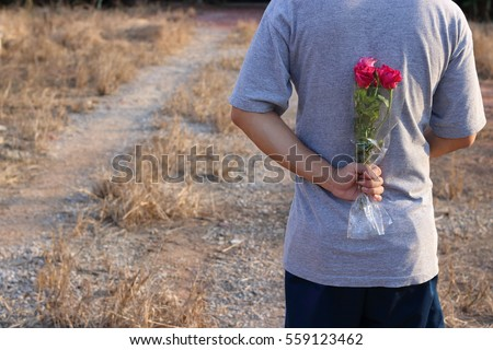 Young man is holding a bouquet of beautiful red roses in his back on countryside blurred background. Romance dating or Valenday's day concept.