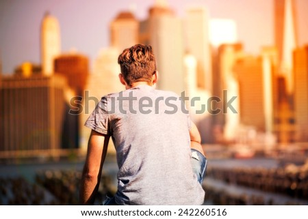Young man is looking at Manhattan  - stock photo