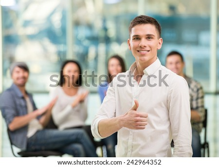 Young man is looking at the camera and a group of people in the background. - stock photo