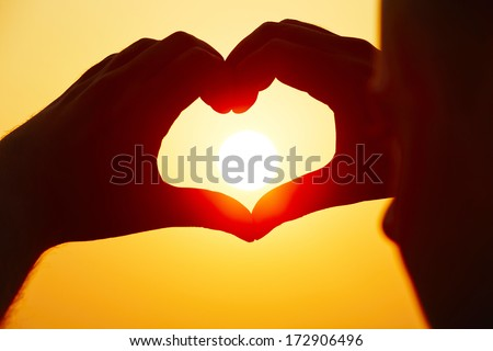 Young man is making heart shape with sun. - stock photo