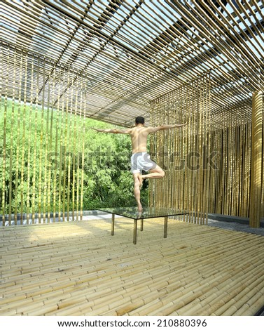 Young man is practicing yoga in bamboo house on green plants background - stock photo