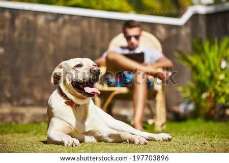 Young man is reading and his dog is resting on the garden.  - stock photo
