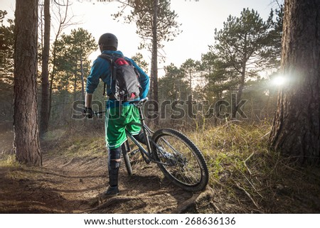 Young man is ready to go on his ATB through the forest trail - stock photo