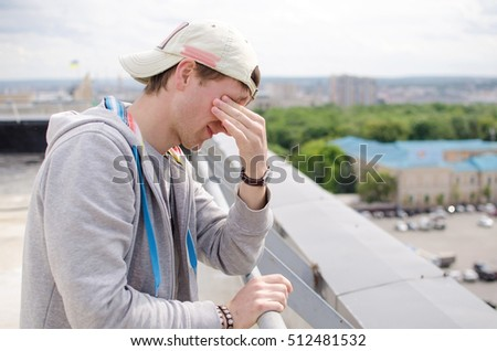 Young man is resting on the roof of the building