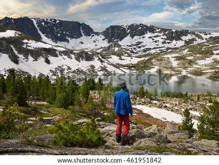 Young man is resting on the top of the ridge of Altai mountains and he is looking into valley full of rocks and lakes with pure clear water during summer tourist trip in holiday.  Russia, Siberia.
