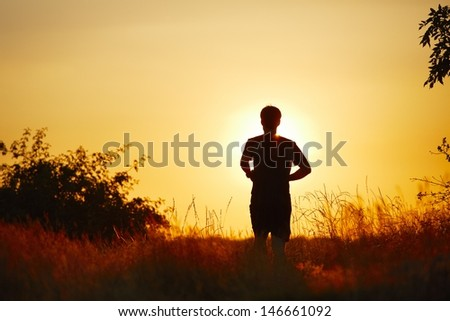 Young man is running at the sunset - back lit  - stock photo