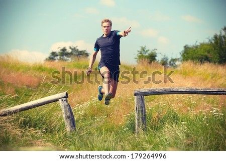 Young man is running in nature - retro color - stock photo