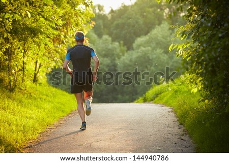 Young man is running on road - sunset back lit - stock photo