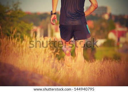 Young man is running on summer meadow - lovely sunset light