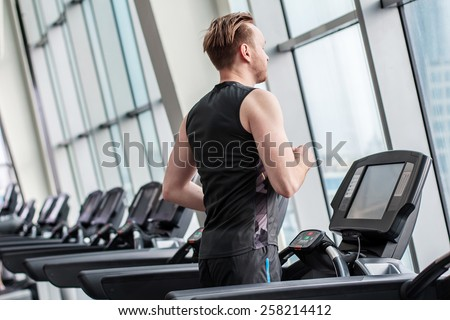 Young man is running on the treadmill in gym