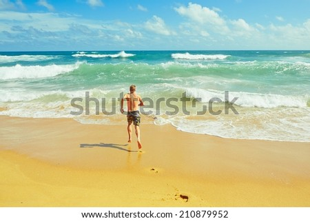 Young man is running to the sea