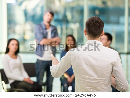 Young man is sharing his problems with people. View of man is telling something and gesturing while group of people are sitting in front of him and listening. - stock photo