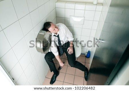 Young man is sitting drunk on a toilette, presumably he is in a club - stock photo