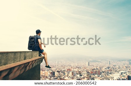 Young man is sitting on a roof and looking city - stock photo